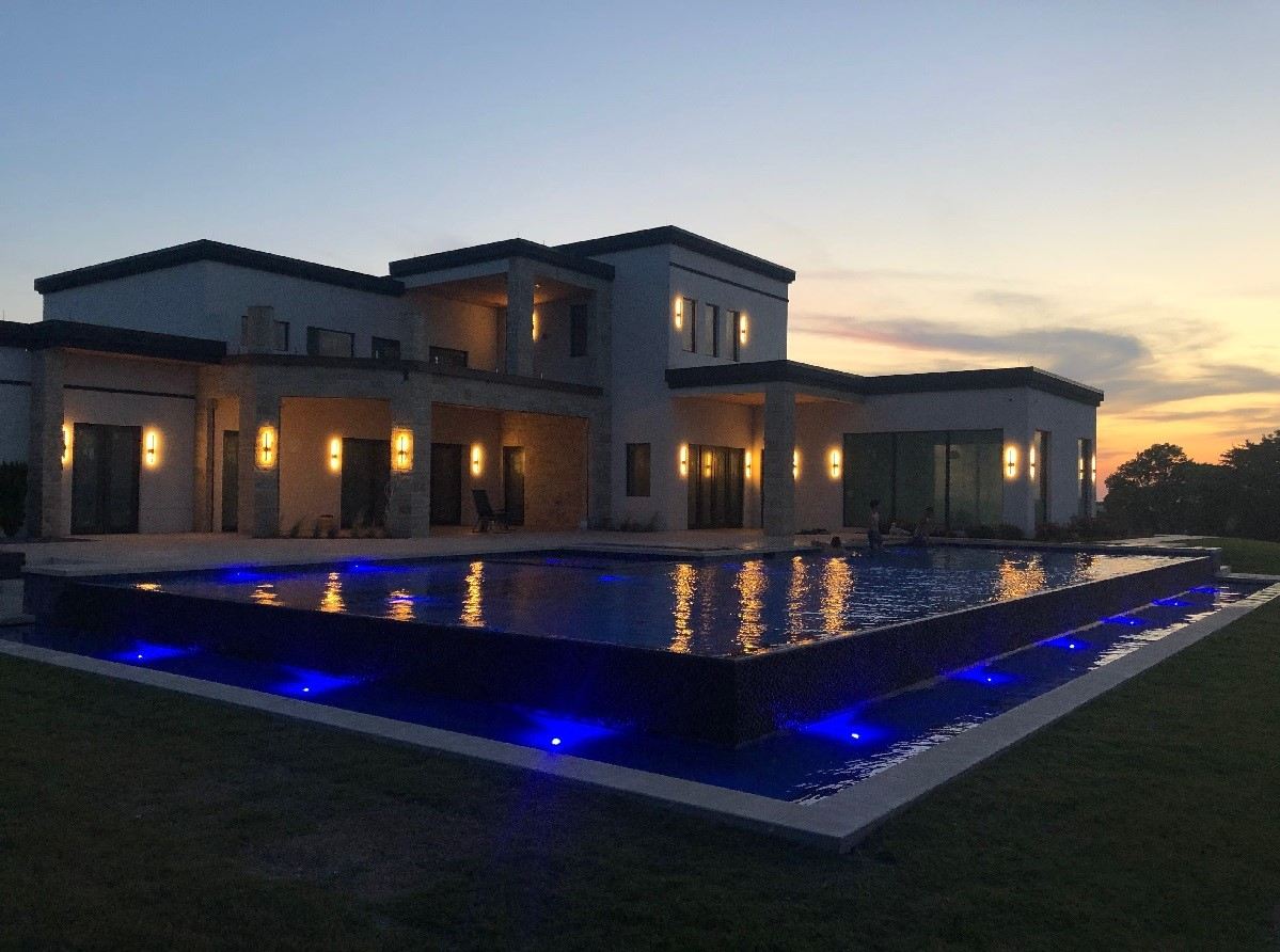 Modern ICF new construction home with infinity edge pool