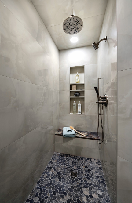 Curbless walk-in shower with quartzite seating and bottle niches